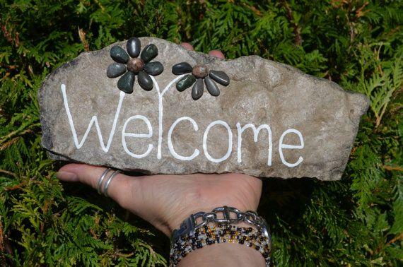 Wunderschöne Stück Fels, handverlesen von mir am Ufer des Lake Huron, gemalt mit dem Wort willkommen auf es, und versammelten sich ein paar Kiesel Blumen von Hand gemacht Strand Kieselsteine vom gleichnamigen See. Wirklich ein wunderbares Einzelstück. Dieses Juwel misst ca. 10 X4 ist signiert und datiert auf der Rückseite von mir und hat einen Anstrich von Lack zu versiegeln und zu schützen aber nicht empfehlenswert für den Dauereinsatz im Freien, wenn die härtere Elemente ausgesetzt, wenn…
