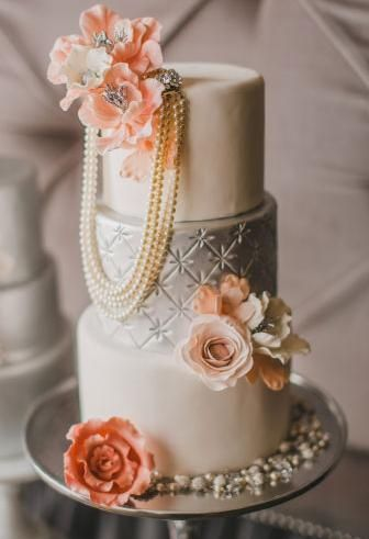 Vintage silver and ivory wedding cake with peach flowers and pearls. Absolutely love this cake, especially with the pearl necklace. Never seen anything like that before.