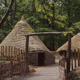 A photograph of a reconstructed Iron Age Celt round houses in a village setting