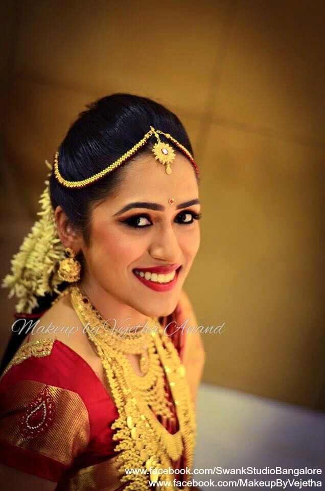 Our bride Bhavya is all smiles after her bridal makeover for her muhurtam. Makeup and hairstyle by Vejetha for Swank Studio. PHOTO CREDIT: Manish Ananda. Traditional Southern Indian bride. Bridal hairstyle. Bridal jewellery. Red lips. Maang tikka. Jhumkis. Silk sari. Tamil bride. Telugu bride. Kannada bride. Hindu bride. Malayalee bride. Bridal Saree Blouse Design. Indian Bridal Makeup. Indian Bride. Gold Jewellery. Statement Blouse. Find us at https://www.facebook.com/SwankStudioBangalore