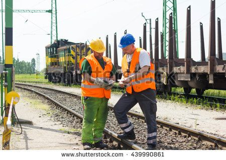 Rail workers coordinating cargo loading to transport train on the tracks. Railway employees in safety west and helmet talking about instructions.