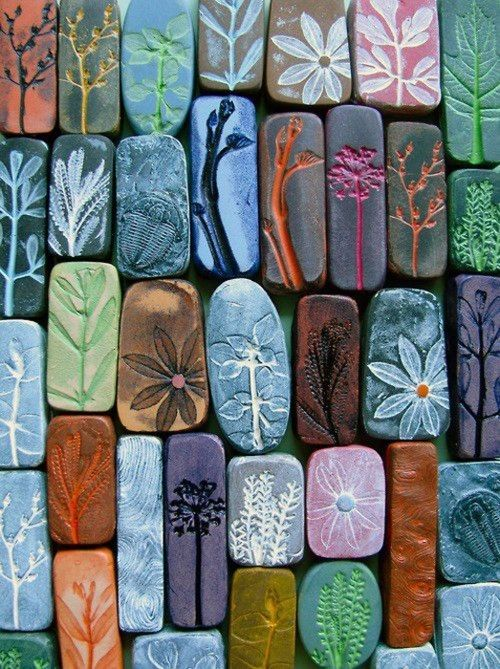 """Flower and stem impressions on what appear to be DIY concrete """"stones"""".  Love all the color and different patterns."""