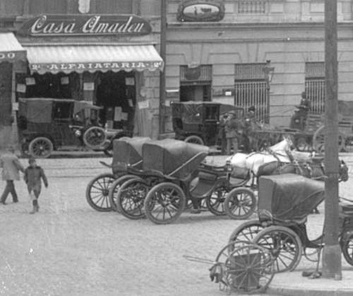1916 - Largo da antiga Catedral da Sé. Na época era estacionamento de carros de aluguel. Na foto, carros de aluguel estacionados em frente à Alfaiataria Casa Amadeu.