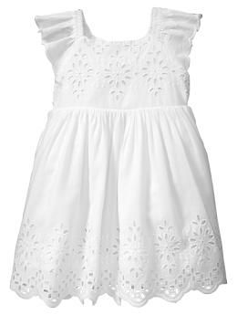 Scalloped eyelet dress. Short flutter sleeves with scallope trim.  Round neckline.  Floral eyelet detailing at bodice and hem.  Scalloped trim at hem.  Fully lined.  Includes a diaper cover. $36.95