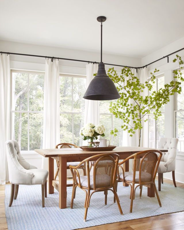 the sun-drenched dining room offers up ample country views, including a pasture for baby foals. To highlight the scenery, Lauren outfitted the room with understated ivory curtain panels hung from sleek wraparound rods. (The drapery hardware may look high-end but was actually purchased at Ikea for less than $50.) A weathered French pendant spotlights the most sentimental piece in the room: a dining table that Lauren's husband, Chad, crafted using reclaimed wood from her father's barn.
