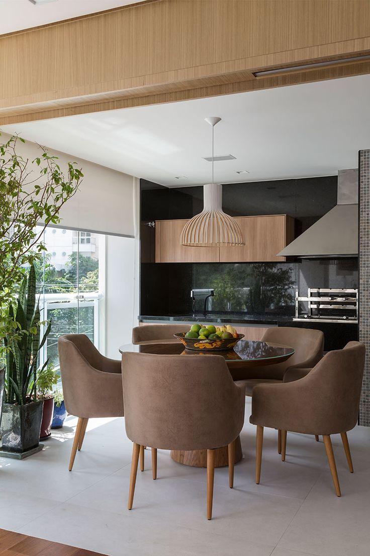 Decoração de apartamento moderno e integrado. Na varanda mesa de jantar redonda de madeira e vidro com cadeiras estofadas.