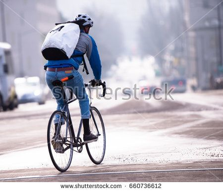 A man in protective helmet and with a backpack behind enjoys riding a road bike through the streets of a modern urban city, in which there is a place for bikers - enthusiasts of a healthy lifestyle