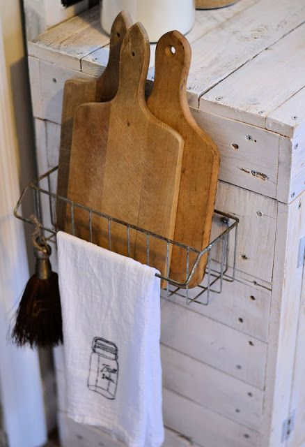 Hanging Wire Basket on the side of a kitchen cabinet for storing cutting boards, etc.