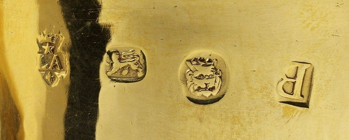London gold hallmarks for 1717-18, left to right: maker or sponsor mark for Paul De Lamerie; lion passant used to denote either sterling silver or 22ct gold; crowned lion or leopard head for the London Goldsmiths Company; date letter B for 1717-18.  (See more of De Lamerie's work here: http://www.vam.ac.uk/content/articles/s/paul-de-lamerie-objects/)  The cup is in the form of a caudle cup or posset cup, both used for spiced ales and wines, but it is evident that this example was intended more