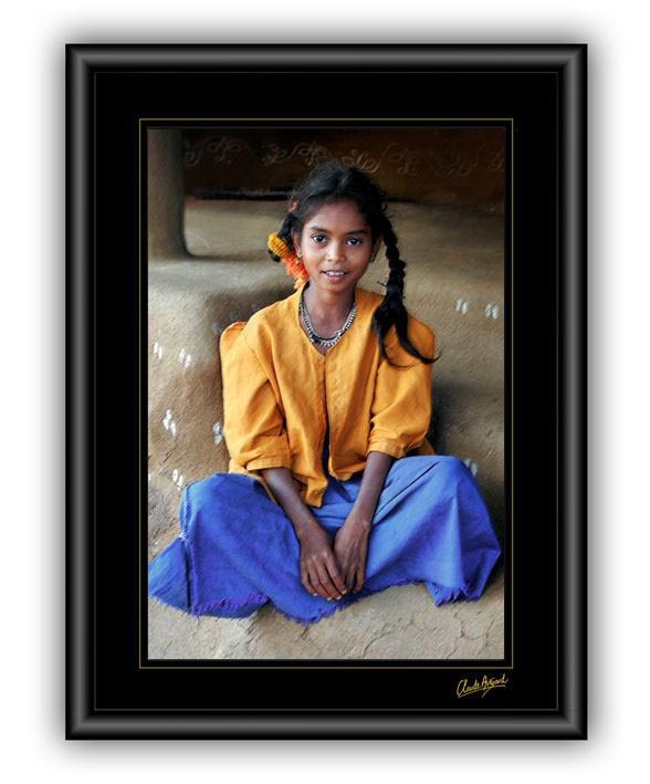Sometimes it is in the eyes of the children – before they have understood the crushing poverty & inescapable future that life reserves for them – that one can still see the total magic of all the possibilities imaginable.  This little girl sits before of her house – its walls are decorated with the more simple, traditional Rangoli designs, painted on with a white lime-and-water paste.  ARAKU Valley – SE India.  © Claude Avézard – All Rights Reserved  http://www.vivendum.info/photo.php?cat=66