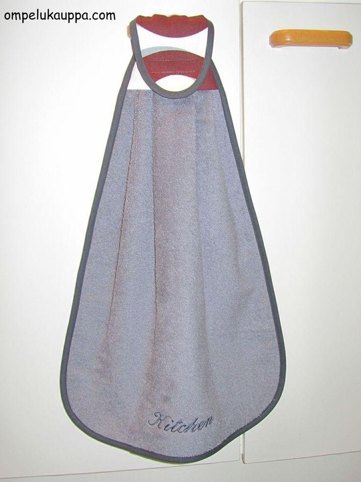Keittiön näppipyyhe tarrakiinnityksellä oven kahvaan. Kokonaiskorkeus 55-60cm. Alaosan leveys 35-40cm. Alaosassa tummanharmaa teksti: Kitchen