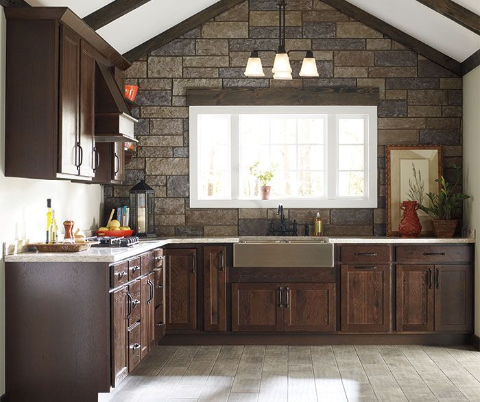 The varied grain and texture of these Emrick Rustic Hickory cabinets melds with the on trend cool brown of the buckboard finish for a look that is rustic yet refined.