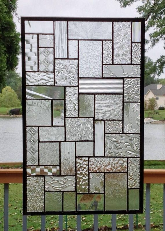 This stained glass panel window is a geometric abstract suncatcher that is done with several different textures of clear glass. The size approximately 18 1/2 x 11 1/2. There are rings so that the piece can be hung in either direction. The patina on the solder is done in black with the zinc