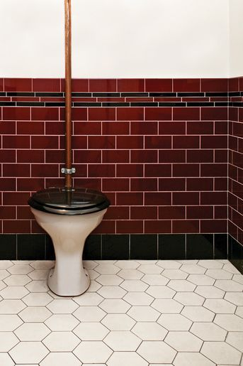 Wc med högspolande toalett och tjugotalsinredning med rött kakel och svart bård. På golvet Victorian floor tiles Barcelona helt i vitt.