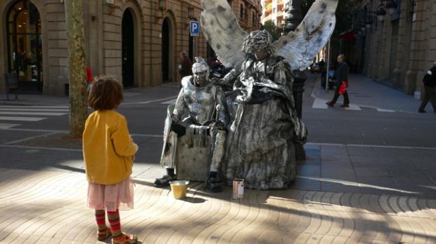 Una bambina osserva un artista di strada sulla Rambla   foto di FK