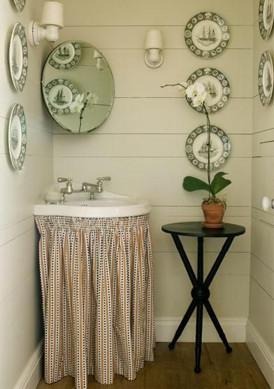 source: Kristin Cunningham    Charming coastal powder room design with skirted bathroom sink, black tripod accent table, round bathroom mirror, decorative glass plates and soft gray walls paint color.