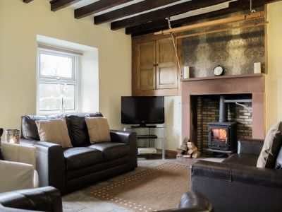 The cosy and inviting lounge at Gable Cottage in Wasdale features quirky ceiling beams and wood burning stove!