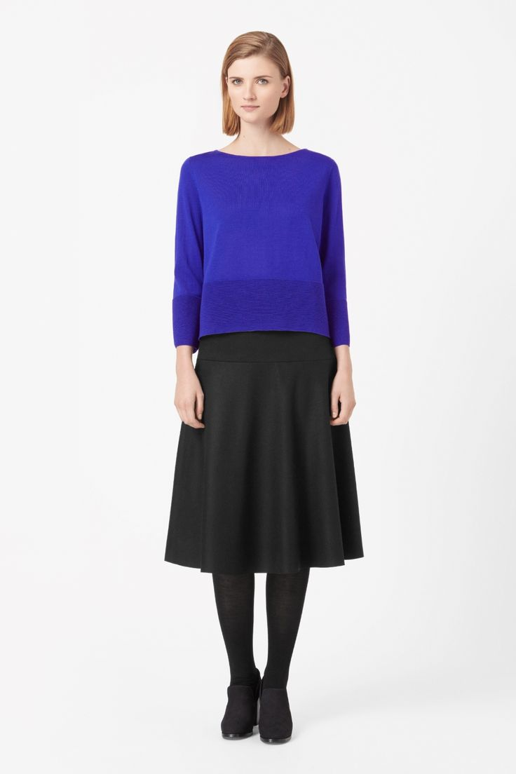 Made from fine merino wool, this jumper has a ripple stitched panel around the hem and cuffs for a modern rib effect. Slightly cropped, it has a wide round neckline and loose 7/8 sleeves.