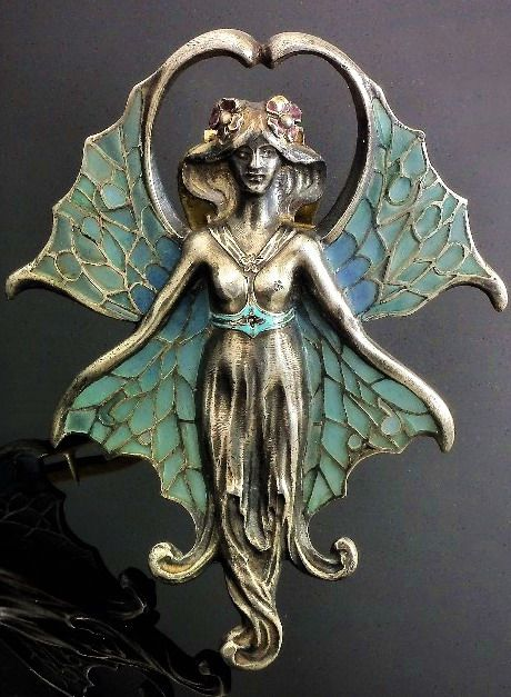An early 20th Century Janvier Quercia silvery metal mounted and plique a jour buckle in the Art Nouveau manner of a winged lightly draped maiden, 65mm x 80mm overall (gross weight 44 grammes), bears Continental marks to reverse