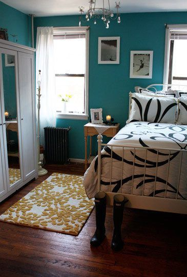 Bedroom with teal walls. I like the wall color with the yellow in the rug.