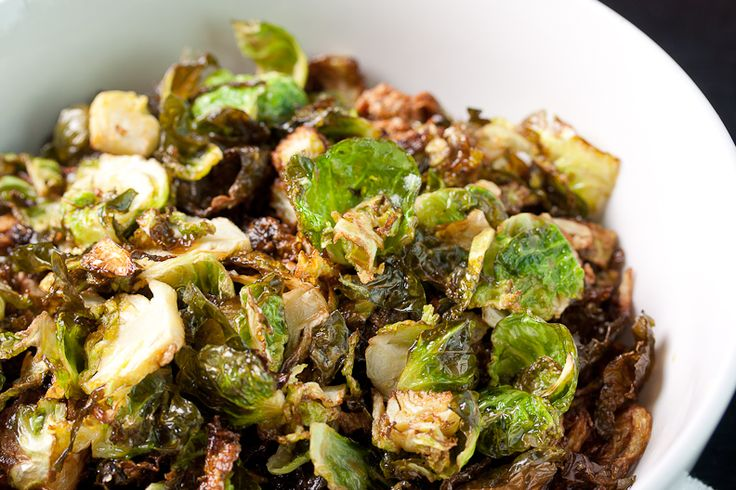 Crispy fried Brussels sprouts -- tossed in balsamic vinegar, topped with crushed garlic cloves, sprinkled with salt and freshly cracked black pepper.