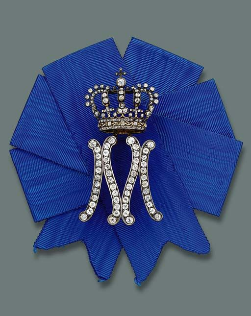 A LADY-IN-WAITING BADGE FOR QUEEN MARIA JOSE OF ITALY, BY MUSY.  Designed as a diamond-set initial 'M' surmounted by a crown on blue silk ribbon, mounted in silver and gold, circa 1930, 7.6 cm. high, in original case with 'M' monogram.