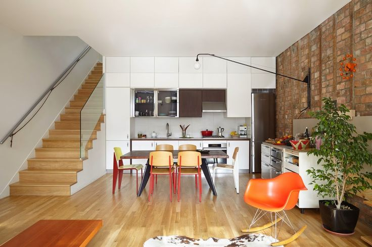 8Home features a minimal, colorful collection of furniture, including a selection of Jean Prouve pieces in the dining room, such as the Standard Chair and EM table, both by Vitra, an orange Eames Rocker, and a classic George Nelson Ball Clock*