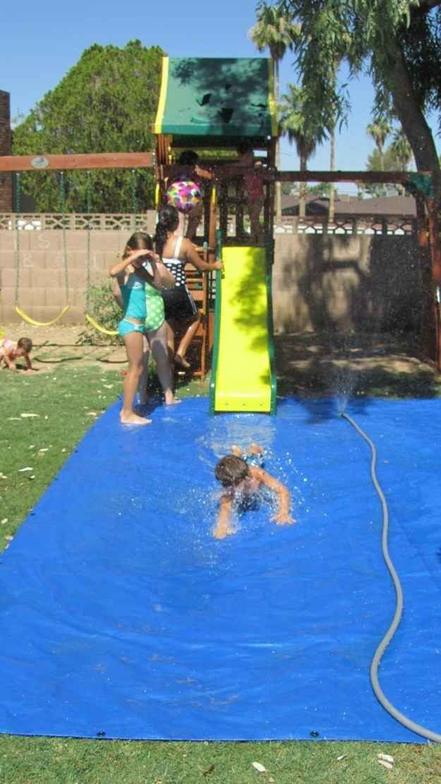 A tarp and sprinkler will create a fun splash pad for a slide. | 51 Budget Backyard DIYs That Are Borderline Genius