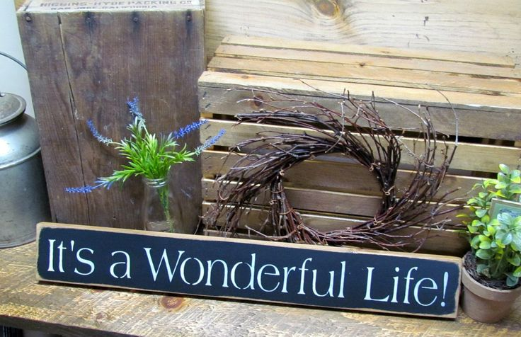 """This wooden sign reads """"It's A Wonderful Life"""". It measures approx 25""""Lx3.5""""H It is painted Black, distressed, stained and sealed. All of our signs are painted, stenciled, sanded and stained by hand."""