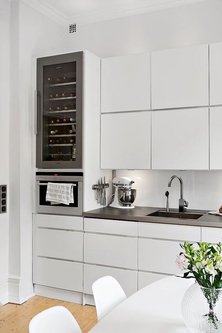 Modular uppers, crisp white slab doors, and built in appliances keep this kitchen modern and chic