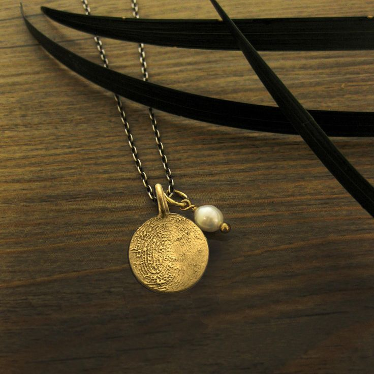 Gold print and oxidized silver chain. Often when loved ones pass away, their fingerprints are taken as a record. We can use these prints to create deeply personal finger print jewellery in gold.