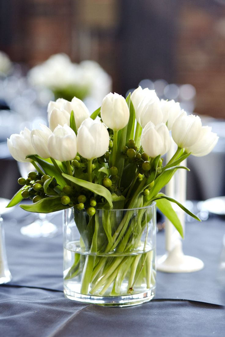 White tulip centrepiece  Green | Grey | White | Black Wedding  Steamwhistle Brewery, Toronto  For all the details, check out http://www.weddinggirl.ca/blog/2013/04/30/james-kyla-04-27-13-steamwhistle-brewery-wedding-toronto/