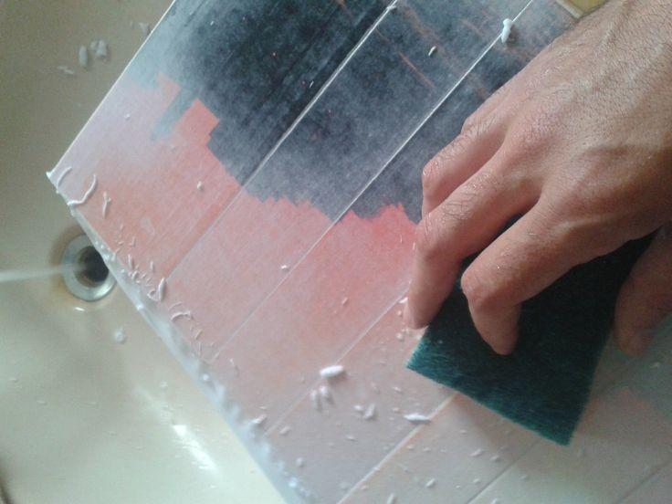 """21 - l'acqua e la spugna servono a rimuovere la carta scoprendo così lo strato di trasparente nel quale man mano vedremo comparire la stampa che dalla carta si è trasferita sulla vernice. Usando poca acqua si rischia di creare troppo attrito e rimuovere la vernice, usarne troppa però significa ammorbidire troppo il legno ed avere lo stesso risultato...misurare bene e ripetere il processo più volte. Questa fase è la più """"critica"""" e darà l'effetto finale di striature sul legno"""