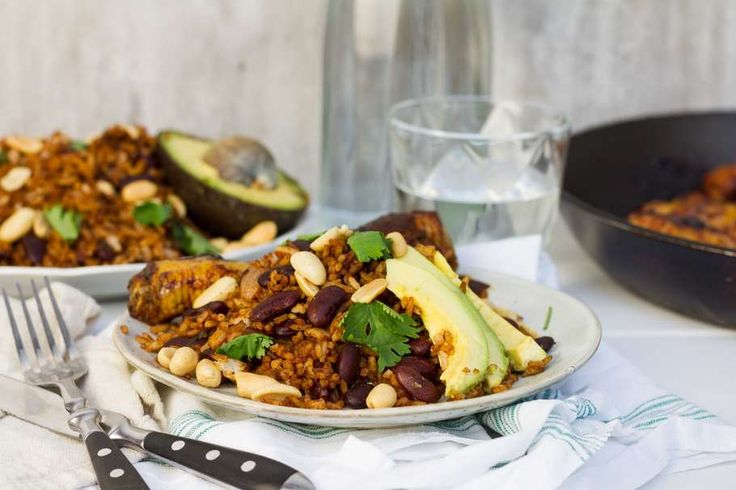 Recept voor antilliaans rijstgerecht voor 4 personen. Met zout, olijfolie, peper, tomatenpuree, kipdrumstick, ketjap manis, knoflook, ui, sojasaus, kidneyboon, pinda's, koriander, avocado en rijst