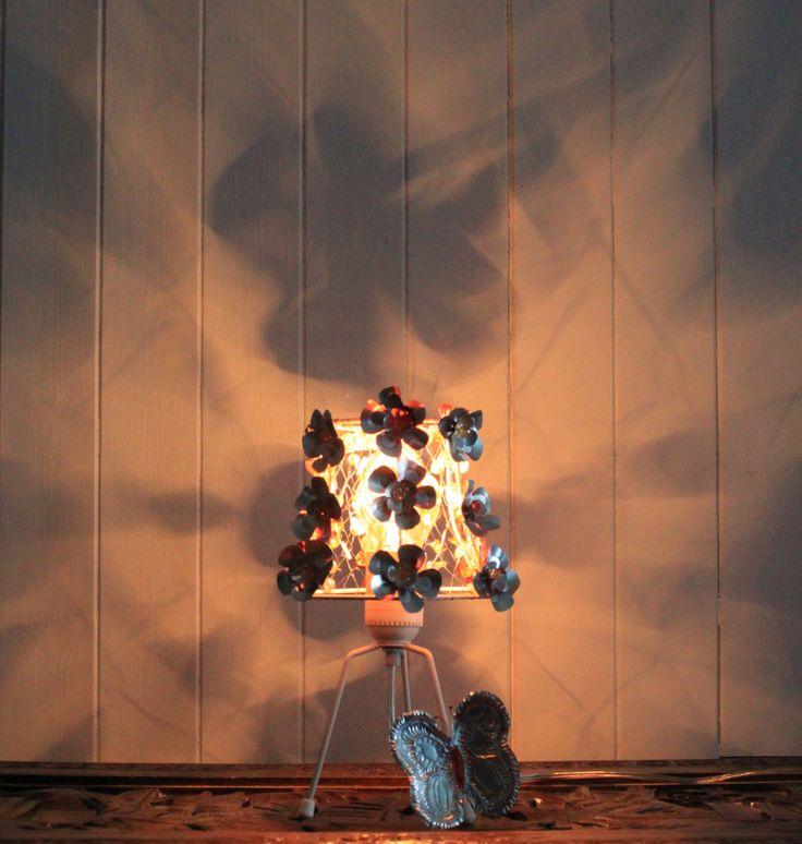 Liss H Guddingsmo. Redesign lampe, blomster av ølbokser, strikket nett med perler på skjermen.