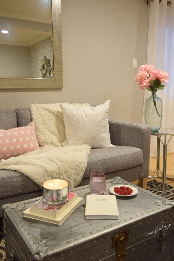 A cozy, feminine space just for you! Soft pink and white accessories, a candle and leather notebook make this the perfect spot to relax and reflect.  HomeGoods, Sponsored Pin.