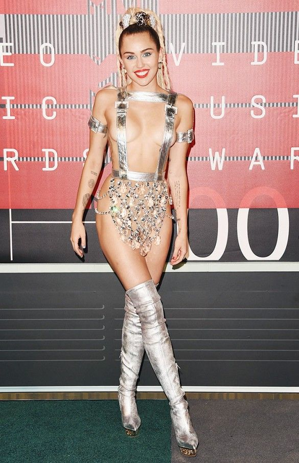 Miley Cyrus wears a custom Versace beaded look with thigh high silver boots