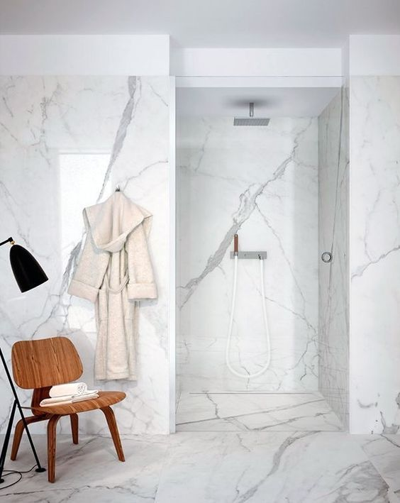 Minimalist bathroom to fall in love with - especially the marble walls and floor. Accented with a walnut colored molded plywood chair. The clear glass door provide a clean, modern look.