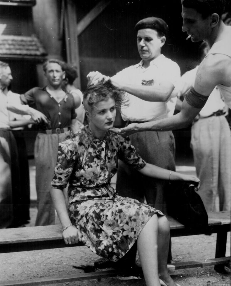 This girl pays the penalty for having had personal relations with the Germans. Here, in the Montelimar area, France, French civilians shave her head as punishment, 1944.