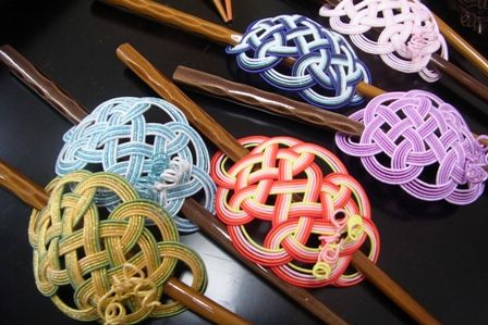 Mizuhiki hair ornaments.  Mizuhiki is a Japanese paper covered cord used to make forms and figures.  Some are Zen-like in their simplicity, others have jaw dropping complexity.