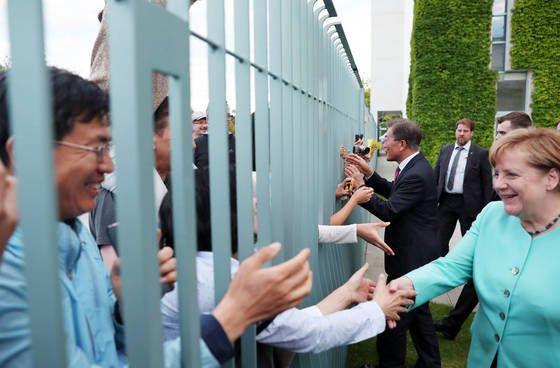 5일 오후(현지시간) 베를린 연방총리실에서 만난 문 대통령과 메르켈 총리가 만찬회담 뒤 총리실 담장 밖에 있는 교민들에게 다가가 인사하고 있다. [청와대사진기자단]