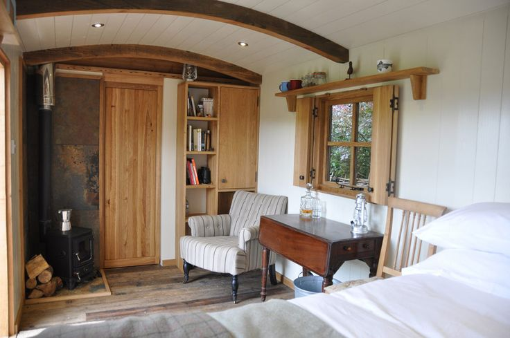 I like the wood floor, wood burning stove, white wood walls, and white+wool bedding -- Gardener's Hut in Scotland [tiny house]