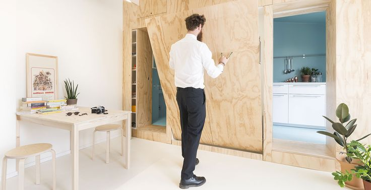 Small 28 square meter apartment in Milan gets modern remodeling which includes a multifunctional furniture piece that hides floating double bed & hides bathroom and kitchen