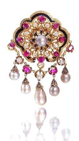 A natural pearl, ruby and diamond brooch, third quarter of the 19th century The openwork cartouche set with a central natural pearl, old brilliant and rose-cut diamonds and cushion-shaped rubies, within a scalloped frame of black enamel and engraved decoration, suspending a swag of similarly cut rubies and diamonds, terminating in a graduating fringe of drop-shaped natural pearls, mounted in yellow gold.