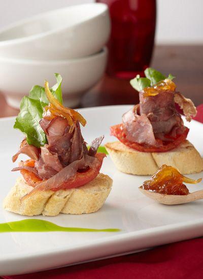 Montaditos de carne oreada santandereana sobre pan francés, con cebollas caramelizadas, tomates confitados y rúgula
