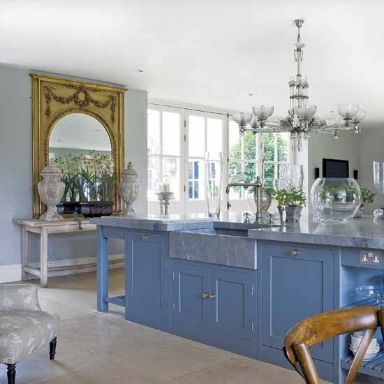 Traditional blue kitchen    The grey marble worktop in this kitchen works perfectly with the sea-blue units. Antique accessories, such as the chandelier and mirror, add a traditional feel.