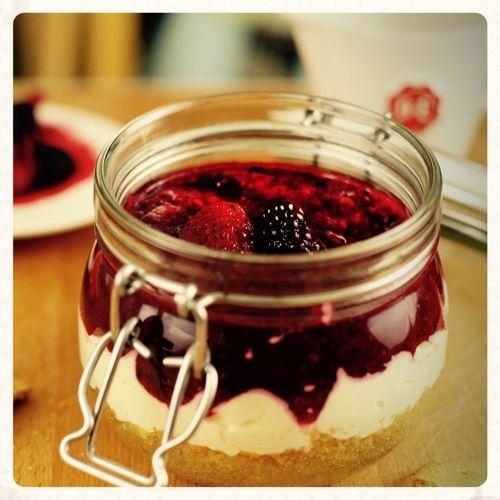 ΥΛΙΚΑ  - 3 μπισκότα digestive - 20 γρ βούτυρο, λιωμένο - 80 γρ κρέμα τυρί - ½ κ. γ. εκχύλισμα βανίλιας - 1 κ. σ. ζάχαρη - φλούδα ½ πορτοκαλιού - 1 κ. σ. χυμό πορτοκαλιού - 100 ml κρέμα γάλακτος 35% λιπαρά - 100 γρ. φρούτα του δάσους, αλεσμένα - 1 ½ κ. γ. άχνη ζάχαρη