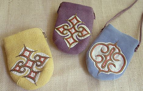 """""""Ainu Embroidery Pouch"""" inspiration came from mitten arm covers Ainu tribes wear at ceremonies. Here, it's interesting to note that Ainu people have a custom of embroidering owl'seyes as motifs on their garments for hands and feet to protect themselves against evil."""