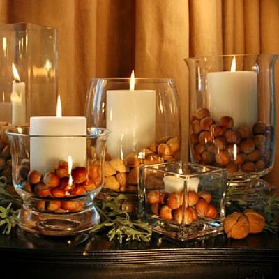 A collection of  various glass containers — hurricane lamps, vases, glasses, and stemware — give your tablescape an interesting topography. Place a candle in the center and will with nuts for a two-step centerpiece.