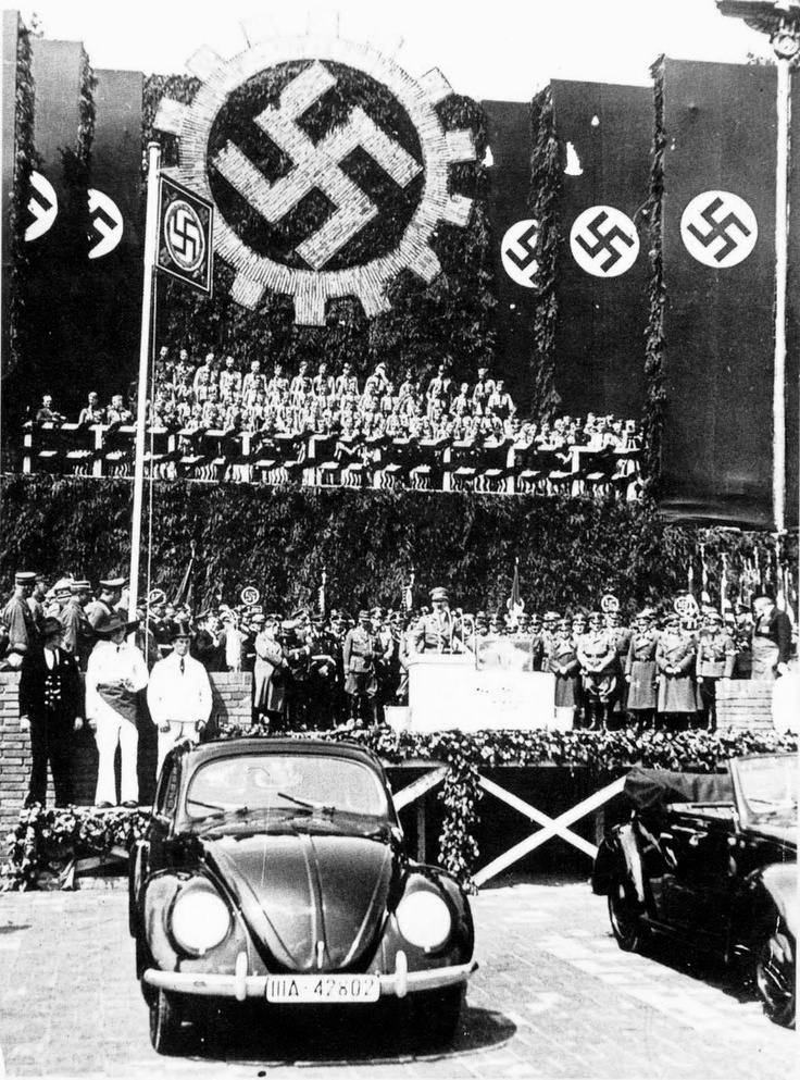 """Hitler presides over the launching of the Beetle. As the country ramped up for war, every German worker was required to put money aside every week for a Volkswagen or """"People's Car"""", designed by Hitler with the help of Ferdinand Porsche. Millions of marks were collected by the Reich in this way, though not a single VW was ever delivered to a contributor. Hitler did present one to Eva Braun as a birthday present, though it's not certain that she ever learned to drive."""